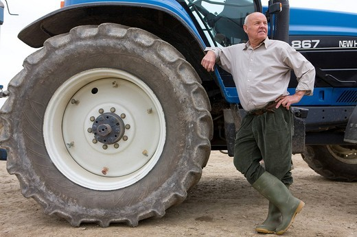 Stock Photo: 4208R-6577 Farmer leaning on tractor