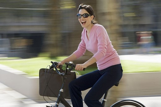 Woman in sunglasses cycling with briefcase in urban area, smiling, side view blurred motion : Stock Photo