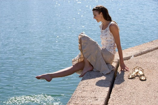 Smiling woman dipping foot in pond : Stock Photo