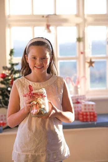 Stock Photo: 4208R-6937 Happy girl holding jar of Christmas cookies