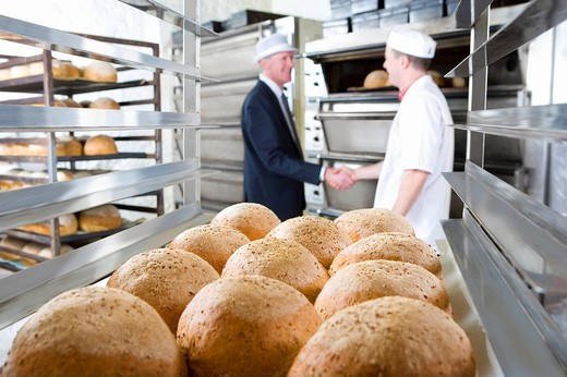 Inspector shaking hands with baker in bakery : Stock Photo