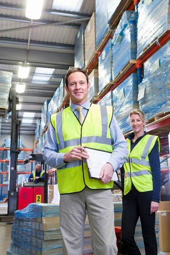 Portrait of smiling warehouse manager and worker with clipboard and pallet truck : Stock Photo