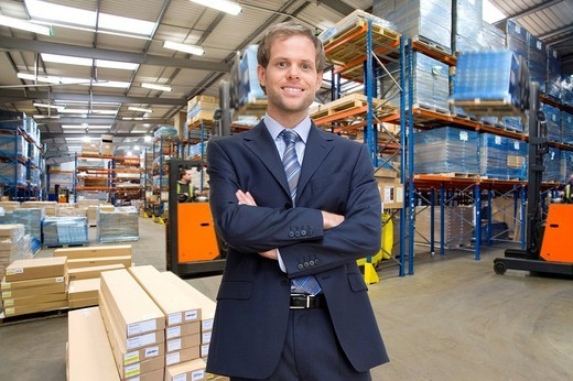 Stock Photo: 4208R-7064 Portrait of smiling businessman with arms crossed in warehouse