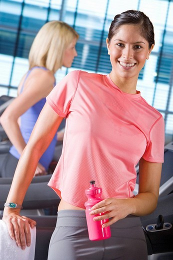 Stock Photo: 4208R-7093 Portrait of smiling woman holding water bottle on treadmill in health club