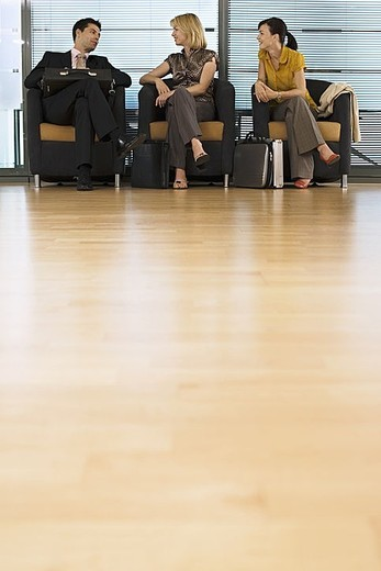 Businessman and two businesswomen sitting in office reception area, talking, surface level : Stock Photo