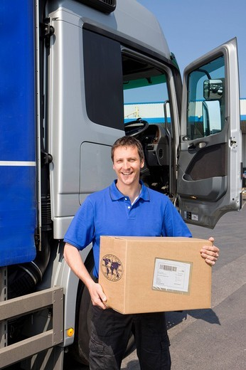 Truck driver standing near semi_truck holding cardboard box : Stock Photo
