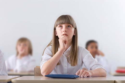 Serious school girl listening in classroom : Stock Photo