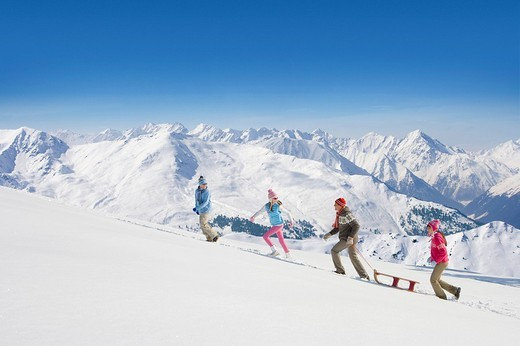 Family pulling sled uphill with mountains in background : Stock Photo