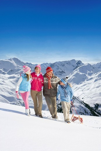 Family standing in snow with sled with mountain in background : Stock Photo