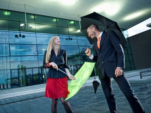A man and a woman holding umbrellas in the rain : Stock Photo