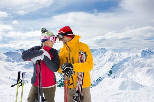 Couple holding skis standing on mountain top together : Stock Photo