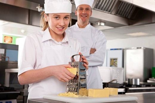 Chef watching trainee grating cheese in commercial kitchen : Stock Photo