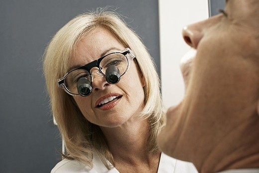 Stock Photo: 4208R-7555 Female dentist wearing surgical loupes, examining patient, close-up differential focus