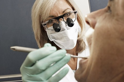 Female dentist wearing surgical loupes and mask, examining patient, using dental tool, close-up : Stock Photo