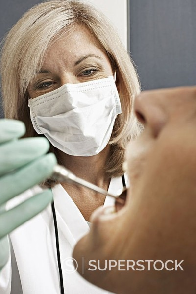 Stock Photo: 4208R-7564 Female dentist wearing surgical mask, examining patient, using angled mirror, close-up