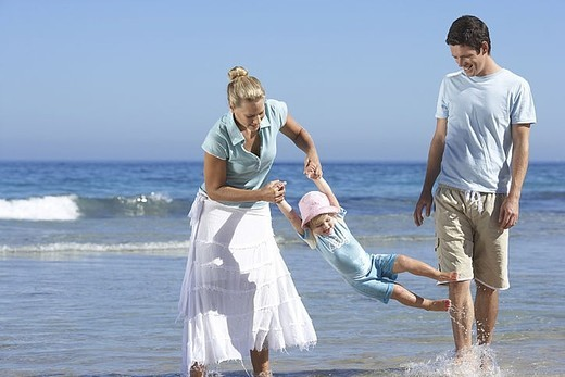 Family walking along beach, ankle deep in water, mother swinging daughter 2-4, smiling : Stock Photo