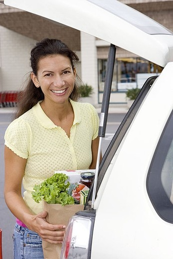 Woman loading car with grocery bags in supermarket car park, smiling, portrait : Stock Photo