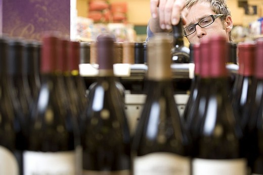 Man shopping for wine in supermarket, choosing bottle from shelf, focus on background : Stock Photo