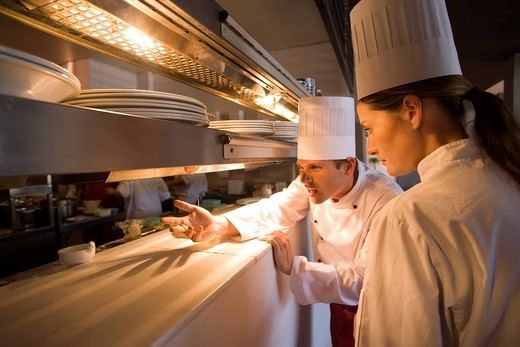 Male and female chefs standing at order counter in commercial kitchen, agitated male chef gesturing to restaurant staff : Stock Photo
