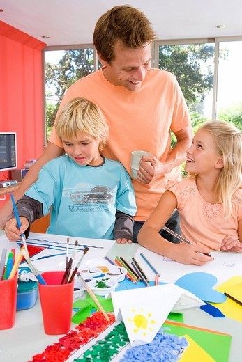 Stock Photo: 4208R-8048 Father standing by son and daughter6-8 sitting at art and crafts table, smiling at daughter