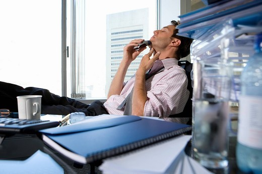 Young businessman shaving at desk in office by book, mug and glass on desk differential focus : Stock Photo