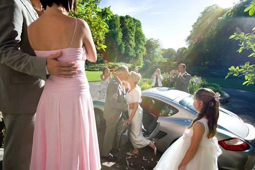 Stock Photo: 4208R-8276 Bride and groom kissing by car, usher, bridesmaid and flower girl 10-12 in foreground lens flare