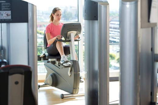 Young woman on exercise machine in gym : Stock Photo