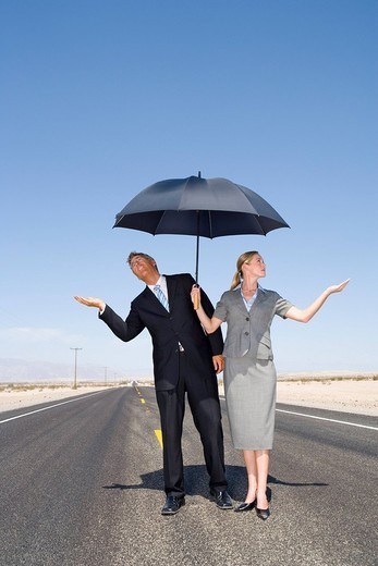 Businessman and woman on open road in desert with umbrella, feeling for rain, low angle view : Stock Photo