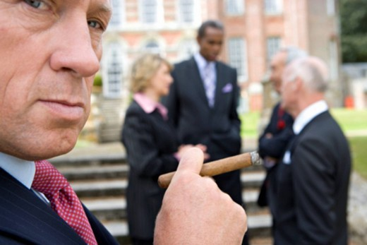 Businessman with cigar by manor house, colleagues in background, close-up : Stock Photo