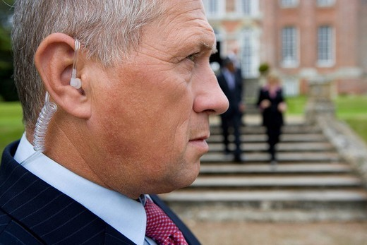 Man with earpiece by manor house, businessmen and women in background, close-up : Stock Photo