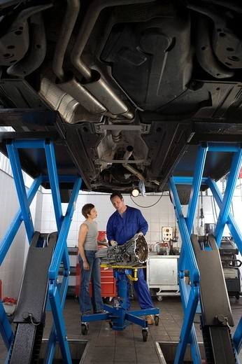 Mechanic with part in conversation with woman by elevated car, low angle view : Stock Photo