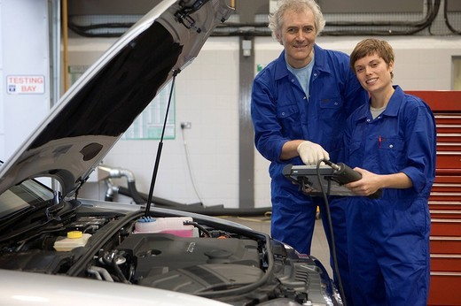 Stock Photo: 4208R-8592 Mechanic and colleague with diagnostic computer by open bonnet of car, smiling, portrait