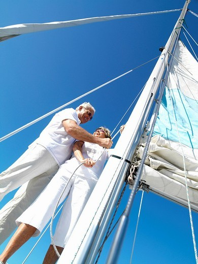 Senior couple erecting sail on yacht, low angle view : Stock Photo