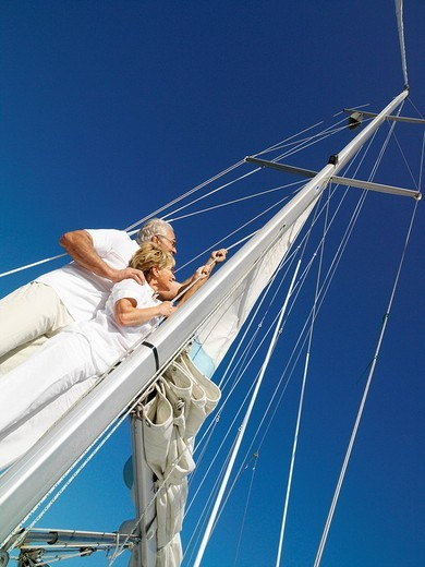 Stock Photo: 4208R-8842 Senior couple erecting sail on yacht, low angle view tilt