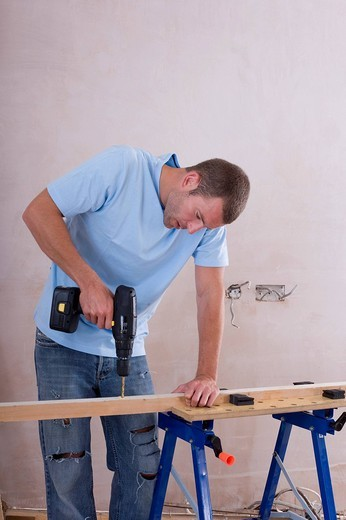 Man drilling wood on sawhorse : Stock Photo