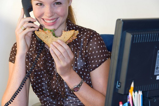 Woman on telephone at desk with sandwich, smiling, portrait : Stock Photo