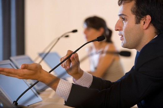 Stock Photo: 4208R-9040 Businessman speaking into microphone at conference