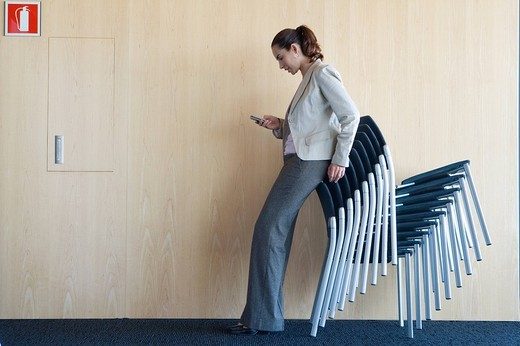 Woman checking text messages while leaning on stack of chairs : Stock Photo