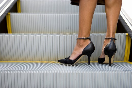 Womanís feet on escalator : Stock Photo