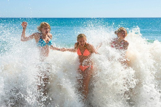 Stock Photo: 4208R-9283 Teenage girls getting splashed by ocean wave