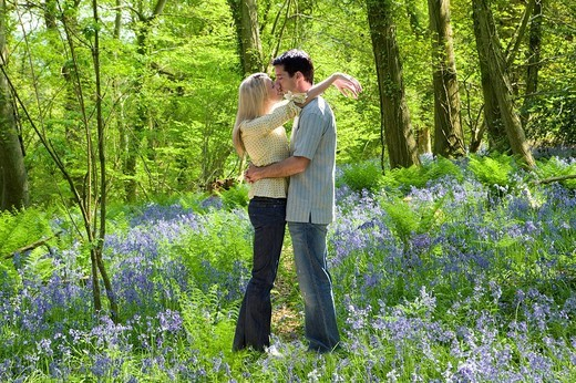 Stock Photo: 4208R-9550 Couple kissing in field of bluebell flowers