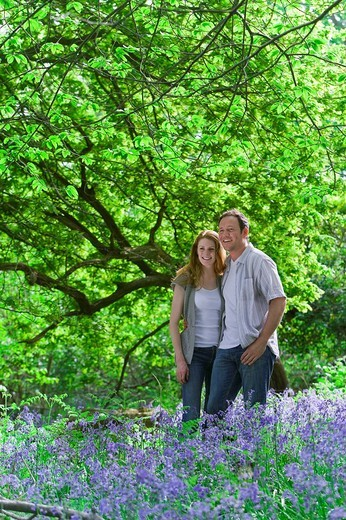 Stock Photo: 4208R-9559 Couple standing in field of bluebell flowers