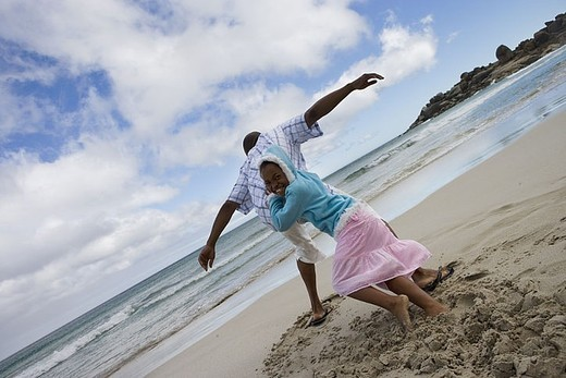 Father and daughter 7-9 playing on sandy beach, girl pushing man, rear view tilt : Stock Photo
