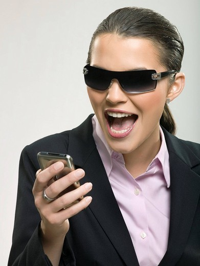 Businesswoman in sunglasses using cell phone : Stock Photo