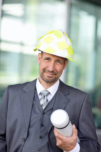 Stock Photo: 4208R-9850 Portrait of mature man in suit wearing hardhat and holding tube container