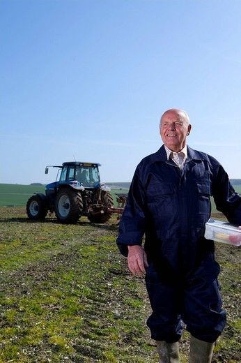 Smiling farmer holding lunchbox in field with tractor and plough in background : Stock Photo