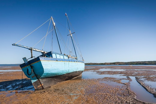 Malagasy dhow. A traditional wooden boat beached at low tide on the sand. Analalava, western Madagascar.  : Stock Photo