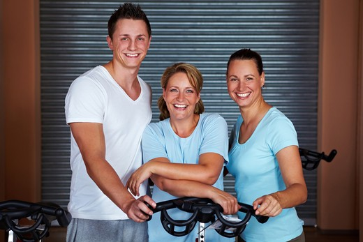 Three happy people standing around spinning bikes in gym : Stock Photo