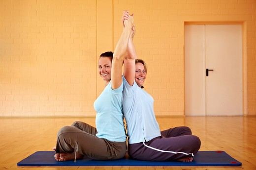 Stock Photo: 4232R-1284 Two happy Best Ager doing back exercises in gym