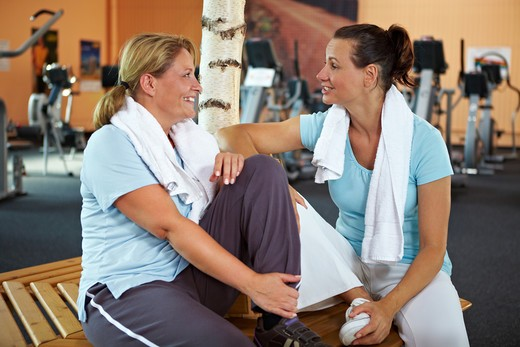 Two happy women talking after their fitness training in gym : Stock Photo